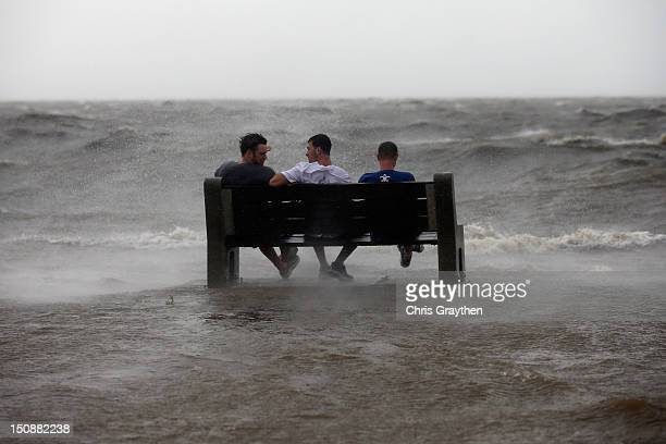 Three men sit on a bench at the edge of Lake Pontchartrain as Hurricane Isaac approaches on August 28 2012 in New Orleans Louisiana Hurricane Isaac...