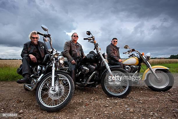 Three men sitting on motorcycles.