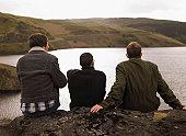 Three men sitting on rock overlooking lake, rear view