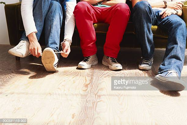Three men sitting on sofa, low section
