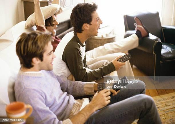 Three men sitting on sofa with remote controls