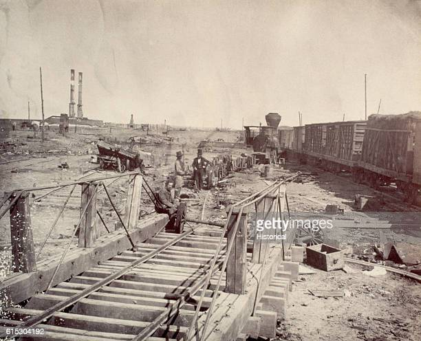 Three men stand amid the wheels and axles that are all that remains of a burned train at Manassas Junction Virginia Throughout 1862 the small...