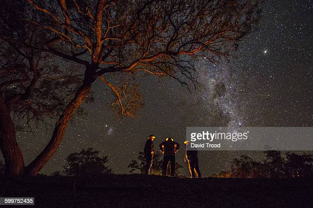 Three men standing by a campfire under the Milky W