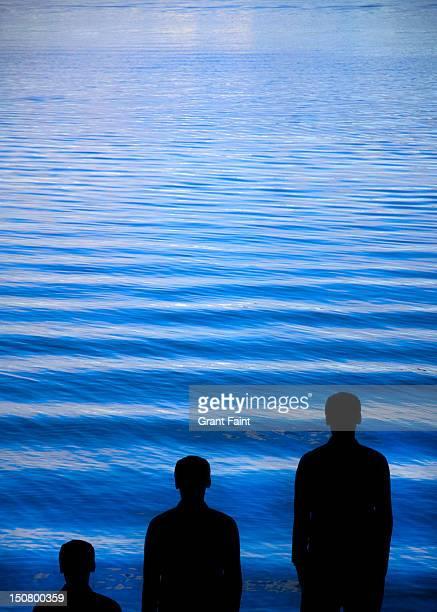 Three men standing by the ocean