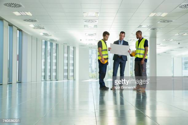 Three men standing in empty office, looking at plans