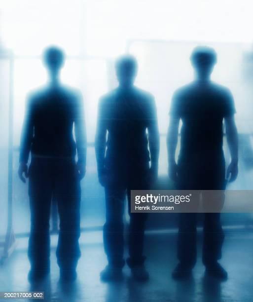 Three men standing in row, by window (defocussed)