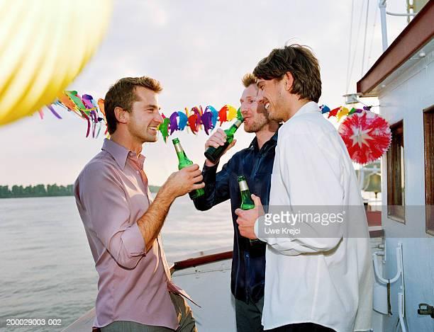 Three men standing on ship deck drinking bottled beer