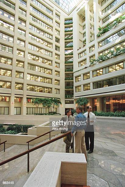 Three men wait at the lobby of International Monetary Fund building September 28 2000 in Washington