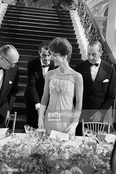Three men wait while Jackie Kennedy is seated at a dinner for the America's Cup Race at the Breakers estate