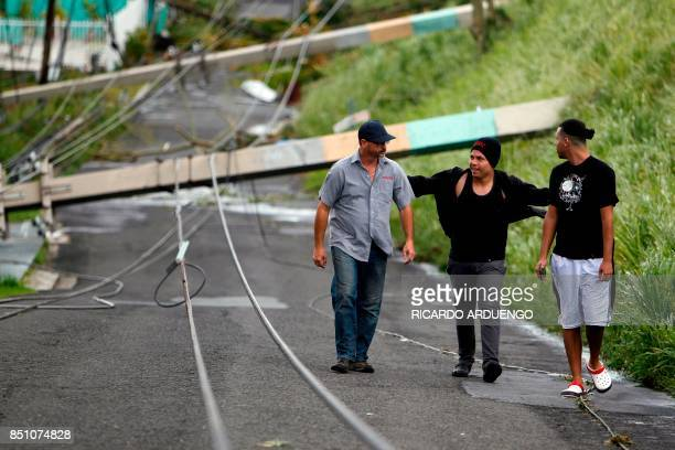 Three men walk between downed power lines in the aftermath of Hurricane Maria in Luquillo Puerto Rico Thursday September 21 2017 Puerto Rico braced...
