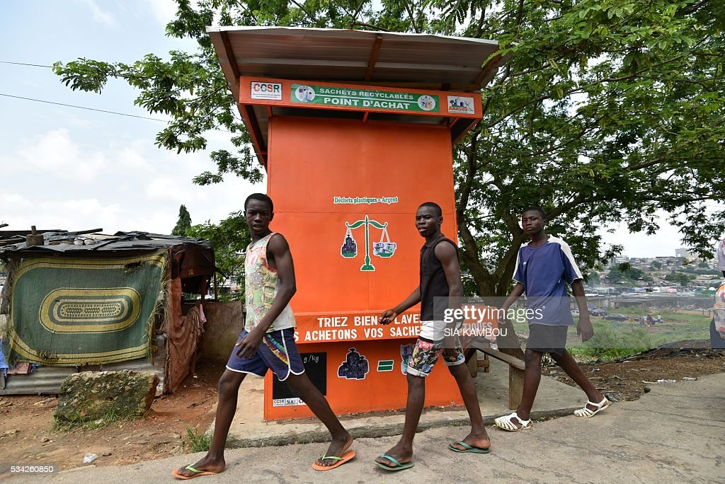 Three men walk past a selling point of plastic waste used to fabricate cobblestone at a waste repurposing facility on May 23, 2016 in Attecoube, Abidjan. / AFP / Sia KAMBOU