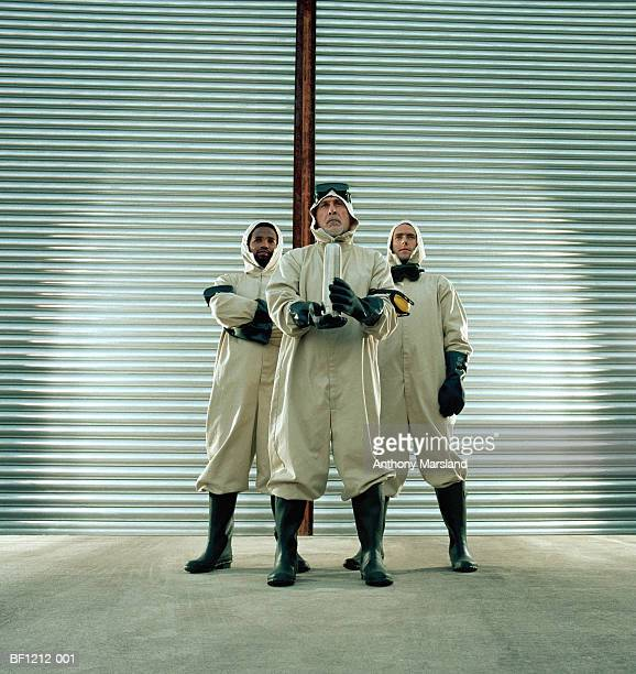 Three men wearing protective gear, one holding metal flask