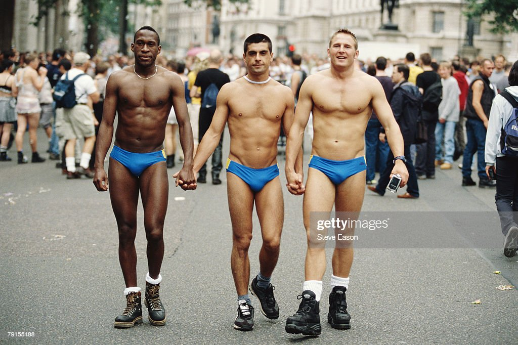 Three men wearing small blue swimming trunks taking part in the London Pride march 1st July 2000