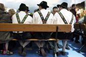 Three men wearing traditional costume sitting on a bench in the exhibition hall of Bavaria at the Gruene Woche agricultural trade fair on January 20...