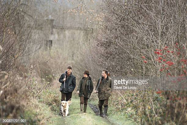 Three men with shotgun and dog walking in forest