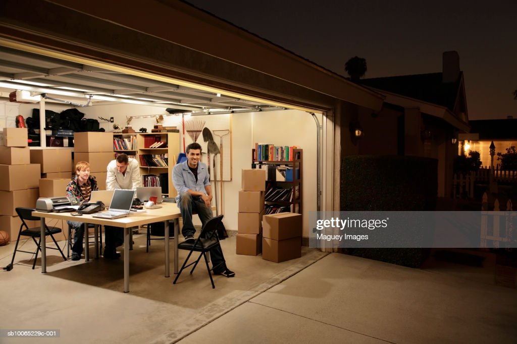 Three men working at laptops on desk in garage at night