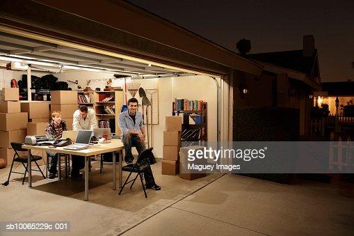 Three men working at laptops on desk in garage at night