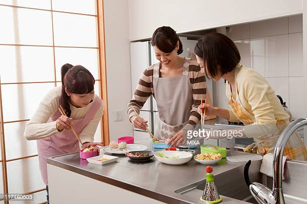 Three mid adult women putting food in lunchbox
