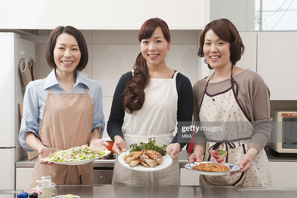 Three mid adult women showing dishes : Stock Photo