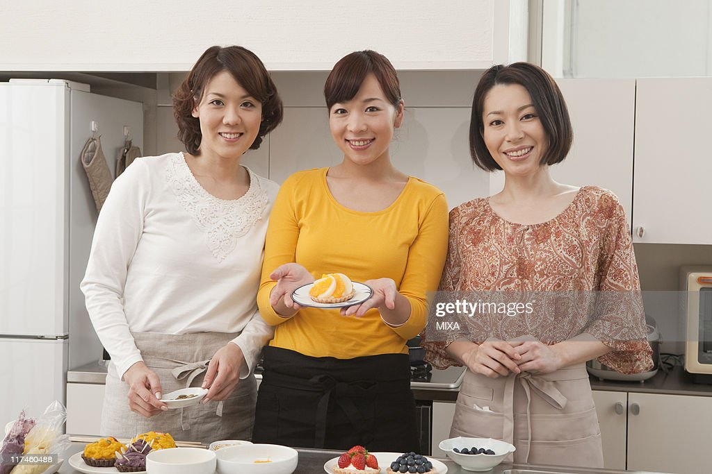 Three mid adult women showing homemade cake : Stock Photo