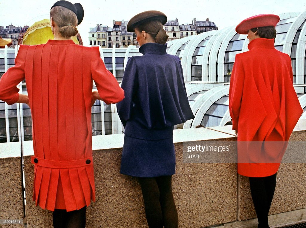 Three models display 'Pierre Cardin' s Backs' : left to right : a Straight dress (at front) in red woolen crepe, pleated at back with a low waist half belt ; a blue tailor suit with wide pleats at back and a red woolen coat, 18 July in Paris for Pierre Cardin 1980/81 Fall/Winter haute-couture collection.