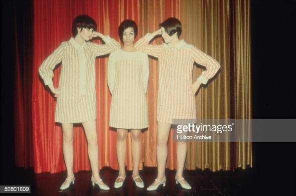 Three models wearing striped mini dresses posing against a curtain mid 1960s
