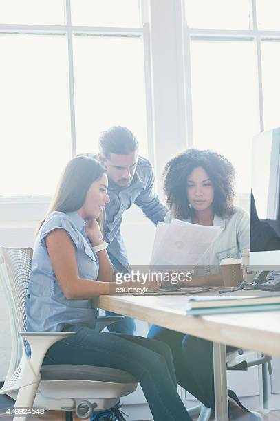 Three modern business people reading a document.