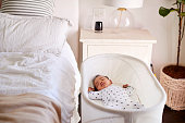 "Three month old baby asleep in his cot beside the bed in his motherâ""u20acs bedroom"
