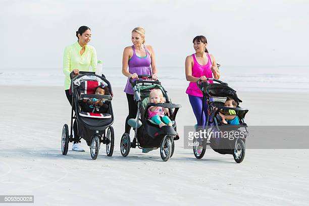 Three mothers and babies in strollers walking on beach