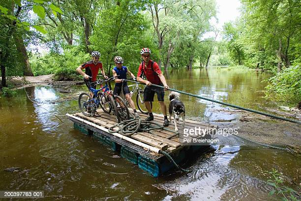 Three mountain bikers with dog crossing river on raft