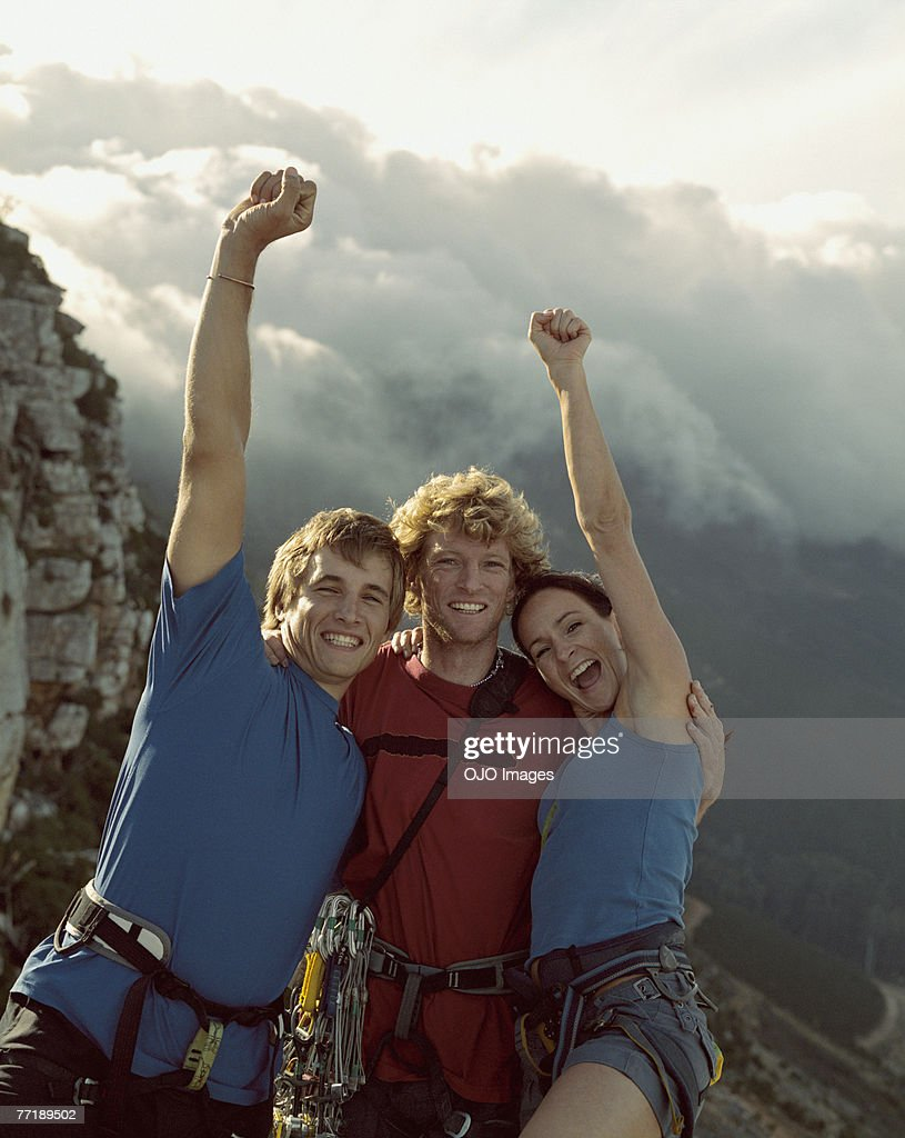 Three mountain climbers with their arms raised in the air : Stock Photo