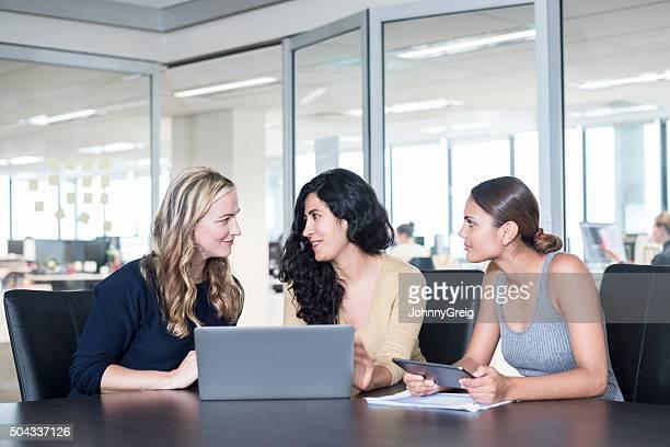 Three multiethnic businesswomen in meeting using laptop