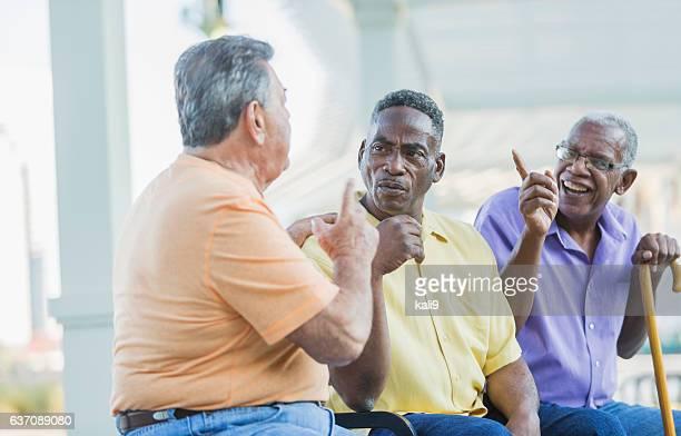 Three multi-ethnic senior men on bench arguing