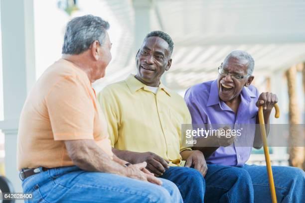 Three multi-ethnic senior men on bench talking, laughing