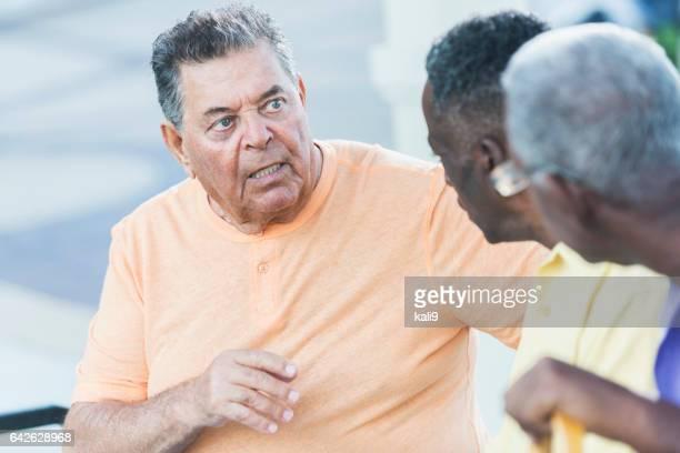 Three multi-ethnic senior men talking