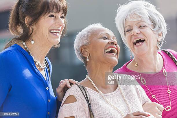 Three multi-ethnic senior women laughing