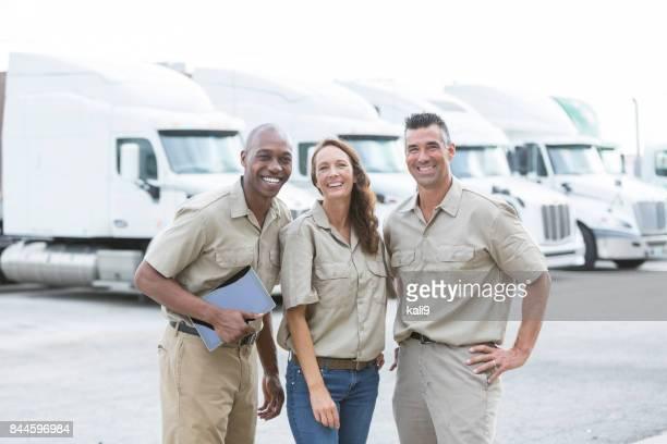 Trois travailleurs multiethniques en face des semi-remorques