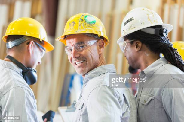 Three multi-ethnic workers in hardhats having meeting
