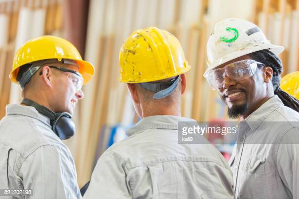 Drie multi-etnische werknemers in hardhats met bijeenkomst