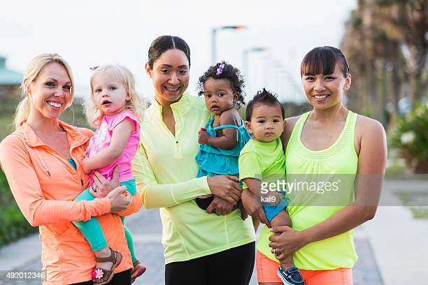 Three multi-racial mothers and their babies outdoors
