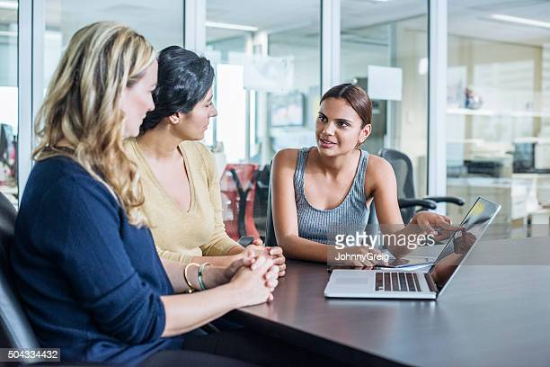 Three multiracial women using laptop computer in modern office