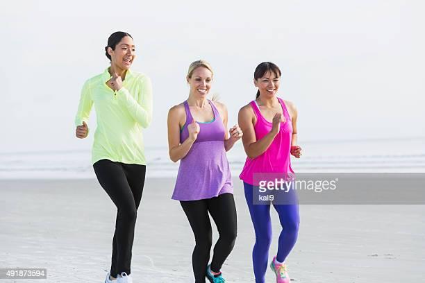 Three multi-racial young women jogging on beach