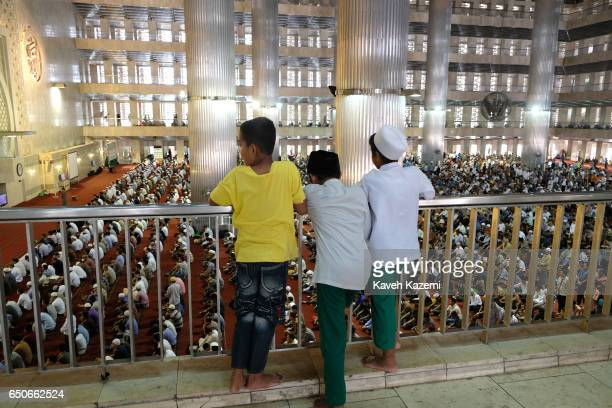 Three Muslim boys watch Friday Prayer ceremony from a balcony in Istiqlal Mosque on November 25 2016 in Jakarta Indonesia Istiqlal Mosque is the...