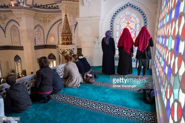 Three Muslim women are seen during midday prayers as visitors sit near them and watch others pray on the ground floor at Sehitlik mosque which is...