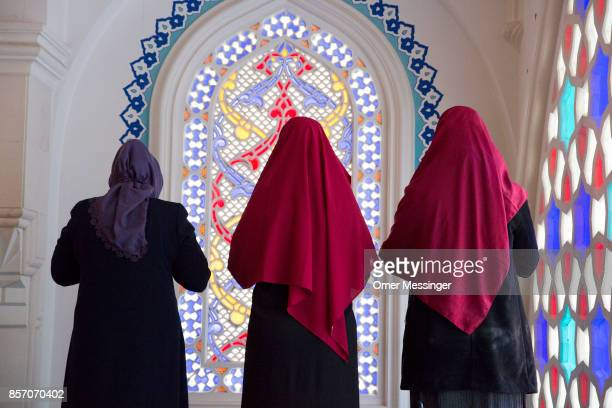 Three Muslim women are seen during midday prayers at Sehitlik mosque which is mostly Turkish on Open Mosque Day on October 3 2017 in Berlin Germany...