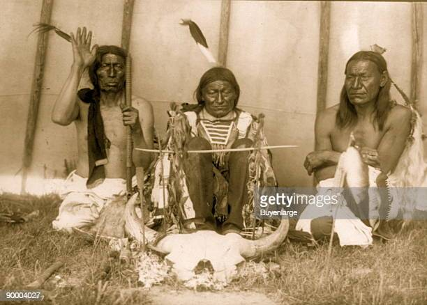 Three Native Americans Slow Bull Saliva and Picket Pin kneeling with bison skull