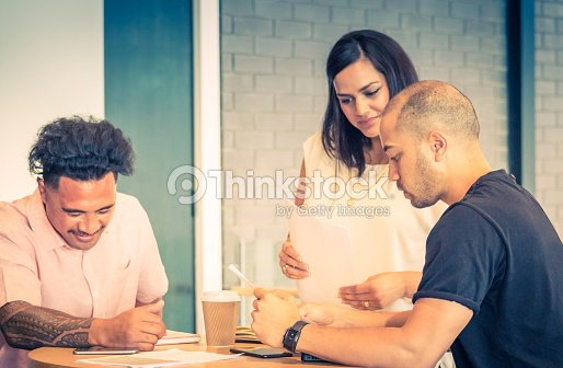 Three New Zealand business people during a work meeting in an office environment. : Stock Photo