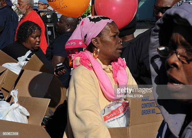 Three of a group of 10000 lowincome and needy people who lined up to receive free Thanksgiving turkeys and fixings distributed by the Jackson...