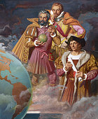 Three of history's most important explorers and discoverersChristopher Columbus Ferdinand Magellan and Vasco de Gama standing with a globe circa 1940...