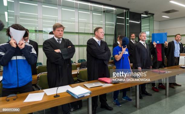 Three of six young men accused of setting fire to a sleeping homeless man hide their faces as they wait for their trial at court in Berlin on June 13...